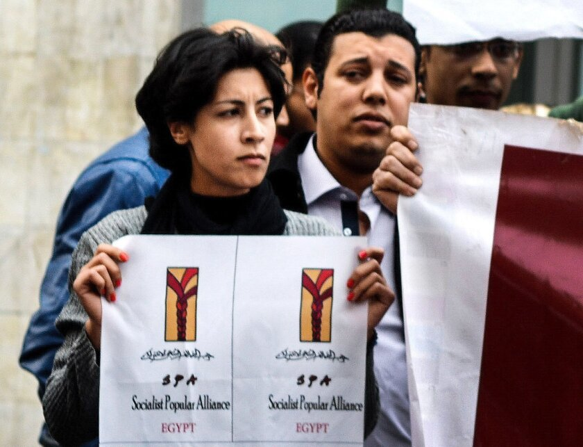 FILE - In this Jan. 24, 2015 photo, 32-year-old mother Shaimaa el-Sabbagh holds a poster during a protest in downtown Cairo. Egypt's highest appeals court on Sunday, Feb. 14, 2016 overturned the conviction of a police officer sentenced to 15 years in prison for the killing of a el-Sabbagh in a Janu