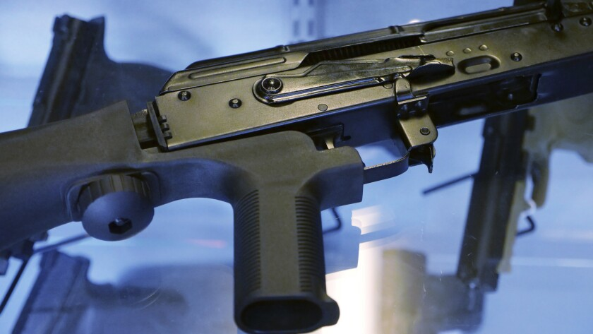 """In this Oct. 4, 2017, photo, a device called a """"bump stock"""" is attached to a semi-automatic rifle at"""