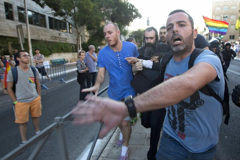 Plainclothes Israeli police detain an ultra-Orthodox Jew after he attacked people with a knife during a Gay Pride parade Thursday, July 30, 2015 in central Jerusalem. Israeli police said several people were stabbed. (AP Photo/Sebastian Scheiner)