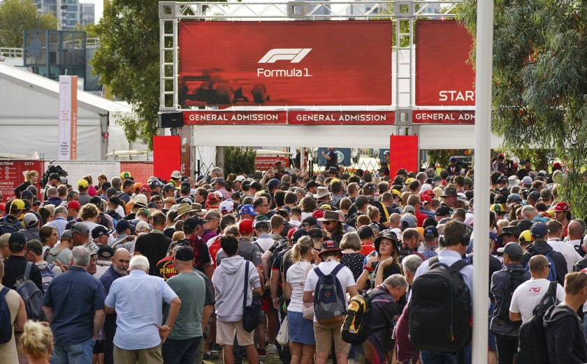 """Spectators line up at a gate to gain entry at the Australian Formula One Grand Prix track in Melbourne, Australia, Friday, March 13, 2020. Victoria state Premier Daniel Andrews said, """"On public health grounds, there will be no spectators at the Grand Prix this weekend - if a race actually happens at all."""" (Scott Barbour/AAP Image via AP)"""