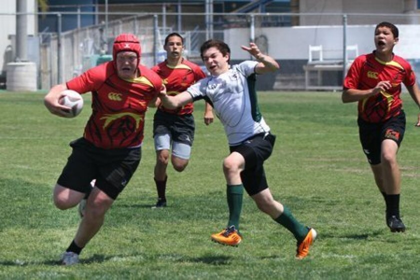 Mustang Aaron Mitchell evades a Fallbrook defender on his way to setup the try of the game. In support are Mustangs Jake Goena and Michael Fogel.