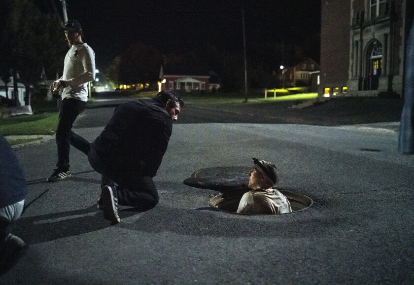 "Director Ben Stiller, kneeling at left, and Paul Dano, in manhole, film a scene from ""Escape At Dannemora"" on location in upstate New York."