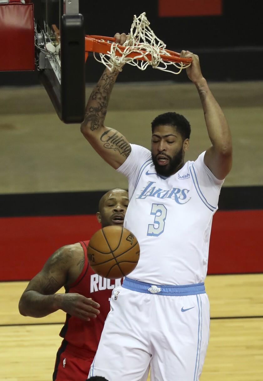 Los Angeles Lakers forward Anthony Davis (3) dunks over Houston Rockets forward P.J. Tucker (17) during the first quarter of an NBA basketball game on Sunday, Jan. 10, 2021, at Toyota Center in Houston. (Brett Coomer/Houston Chronicle via AP)