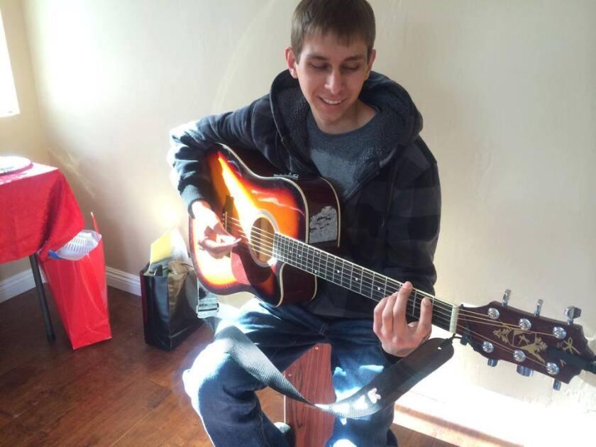 """Elijah """"Bear"""" Diaz playing his guitar"""