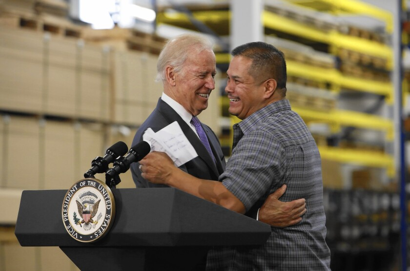 Joe Biden embraces a man behind a lectern with the vice presidential seal