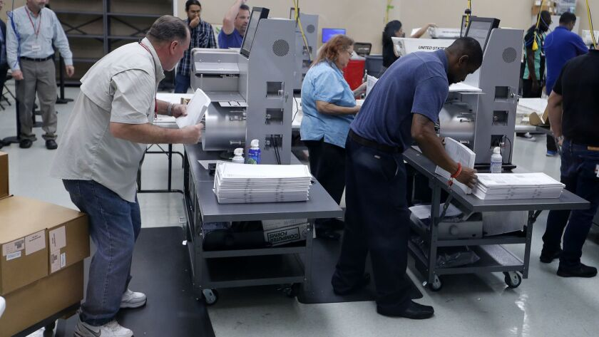 Elections staff load ballots into machine as recounting begins at the Broward County Supervisor of Elections Office on Sunday.