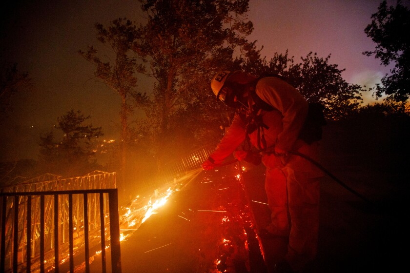 A firefighter uses a garden hose to douse flames.