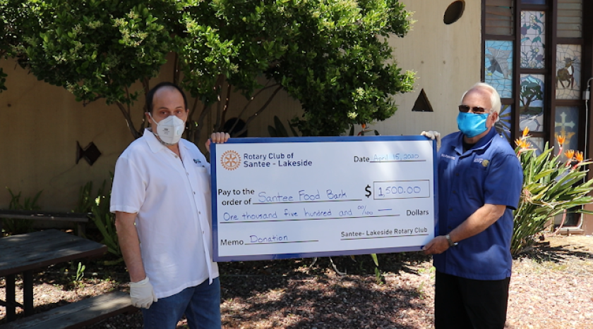 Pastor Dennis Martins, president of the Santee Food Bank (left), and Bill Pommering, president of the Santee-Lakeside Rotary Club, show off a check for $1,500 that came from money donated by club members and Rotary District 5340. The funds will go toward the purchase of food for people in need during the current health emergency.