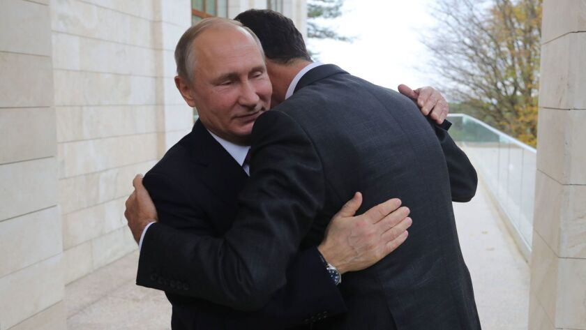 Russia's President Vladimir Putin embraces Syrian counterpart Bashar Assad during a meeting in Sochi, Russia.