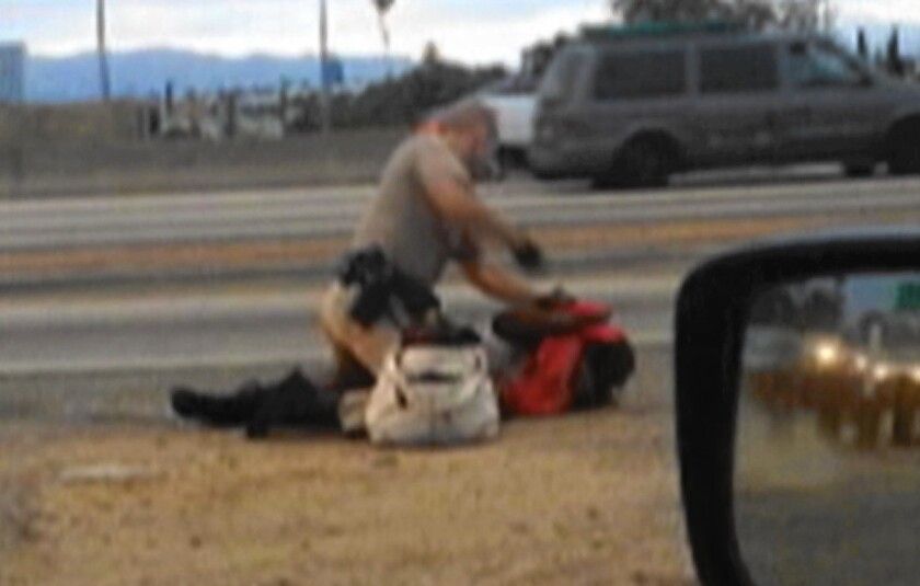 A video made by a motorist shows a California Highway Patrol officer punching Marlene Pinnock by the side of the Santa Monica Freeway.
