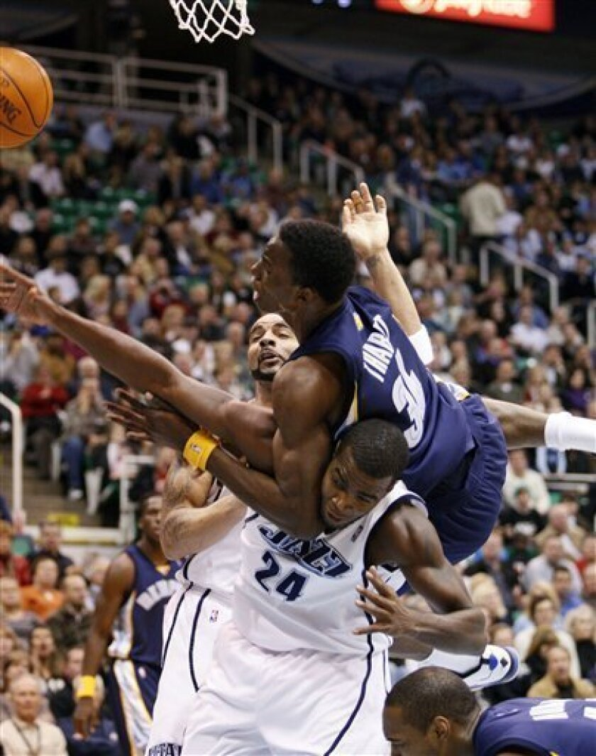 Memphis Grizzlies center Hasheem Thabeet (34) falls on top of Utah Jazz forward Paul Millsap (24) while trying to score as center Carlos Boozer (5) also defends during the first period of their NBA basketball game Monday  Nov. 30, 2009, in Salt Lake City. (AP Photo/Colin Braley)
