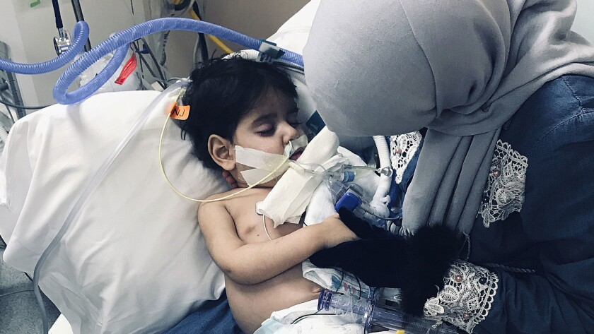 Shaima Swileh holds her dying 2-year-old son, Abdullah, at a hospital in Oakland. Swileh, a Yemeni mother who fought for the right to see her dying son, arrived Wednesday night after the Trump administration gave her a long-sought waiver to its travel ban.