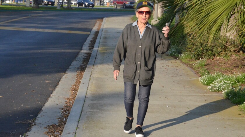 Kathleen Brennan, 91, of Newport Beach takes a brisk walk every day while carrying her transistor radio.