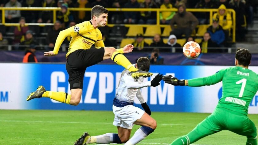 Dortmund's Christian Pulisic, left, clears the ball from Tottenham Hotspur's Erik Lamela, who was trying to score past Dortmund goalkeeper Roman Buerki on March 5.