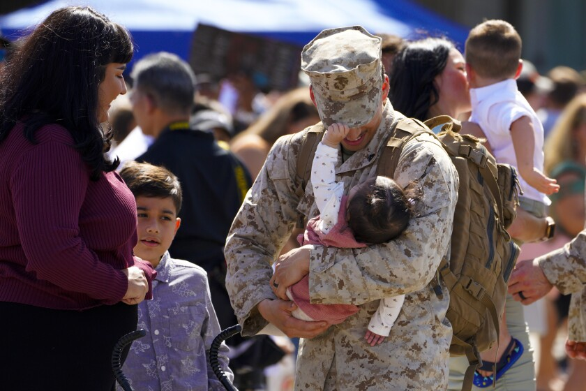 Lance Cpl. Nathan Sweet holds his 8-month-old daughter, Sabrina, as his wife, Selena, and son, Damian, welcome him home.