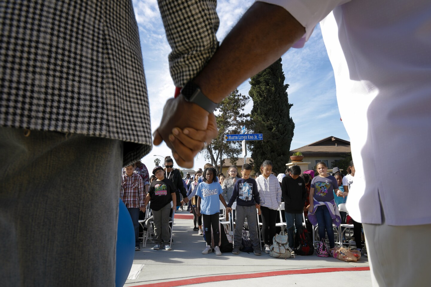 Michael J. Trice (l) and Tommie Vance (r) invite everyone to hold hands during the benediction at the MLK Annual Laying of the Wreath on January 15, 2020 at the Broadway Height community in San Diego.