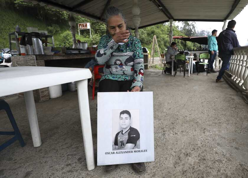 "Doris Tejada, mother of Oscar Alexander Morales who disappeared on New Year's eve 2007, holds a photo of her son, at a shop in Soacha, Colombia, Thursday, April 8, 2021. Tejada and her husband found out that their son indeed is on the list of the ""false positives,"" victims of extrajudicial executions by members of Colombia's army who were falsely presented as guerrillas killed in combat during the country's internal conflict, which ended with the 2016 demobilization of the Revolutionary Armed Forces of Colombia. (AP Photo/Fernando Vergara)"