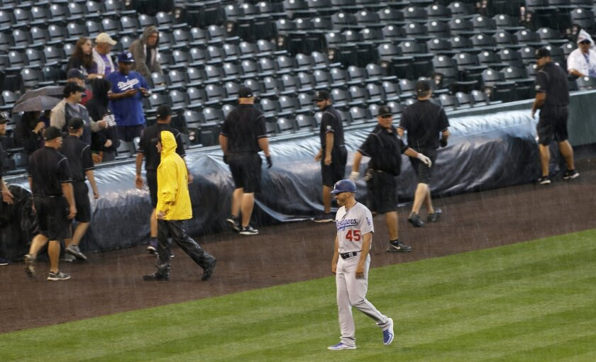 Los Angeles Dodgers third base coach Chris Woodward walks to the dugout, smiling in the rain, as the grounds crew runs for the tarp before the Dodgers' baseball game against the Colorado Rockies on Tuesday, Aug. 30, 2016, in Denver. (AP Photo/Jack Dempsey)