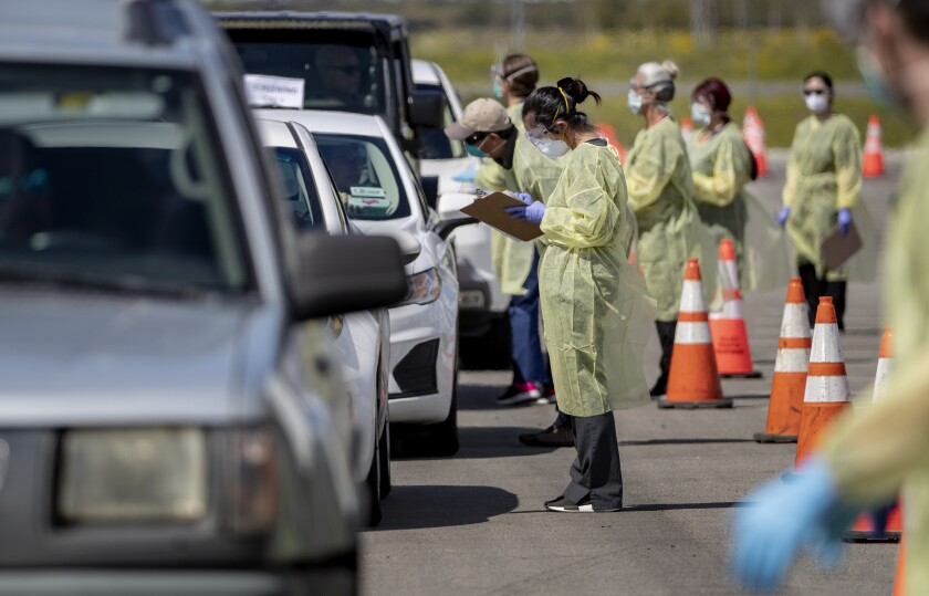 Drivers line up to get a coronavirus test administered by Riverside County medical personnel at Diamond Stadium in Lake Elsinore.