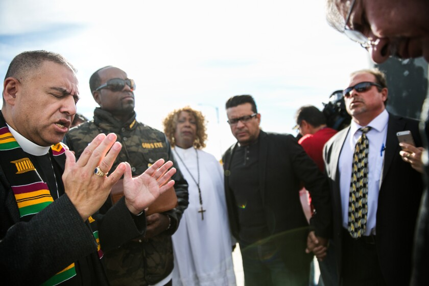 Pastor Juan Carlos Mendez, left, leads a coalition of church leaders as they bow their heads in prayers for the victims of the mass shooting in San Bernardino.