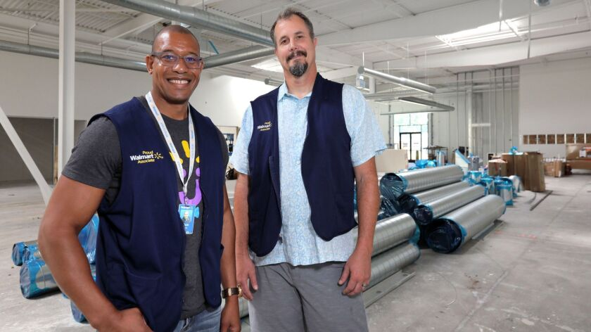 Claude Jones, left, and Bob Lowell, at right, both Senior Directors of Engineering for Walmart Labs, stand where Walmart Labs' San Diego area offices are under construction in the Make campus in Carlsbad.