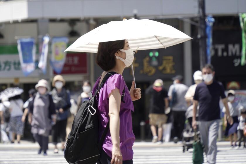 Una mujer con mascarilla para evitar la propagación del coronavirus camina con una sombrilla
