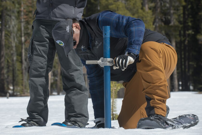 Sean de Guzman, chief of snow surveys for the California Department of Water Resources, checks the depth of the snow pack during the fourth snow survey of the season at Phillips Station near Echo Summit, Calif., Thursday, April 1, 2021. The survey found the snowpack at 49.5 inches deep with a water content of 21 inches. (AP Photo/Randall Benton)