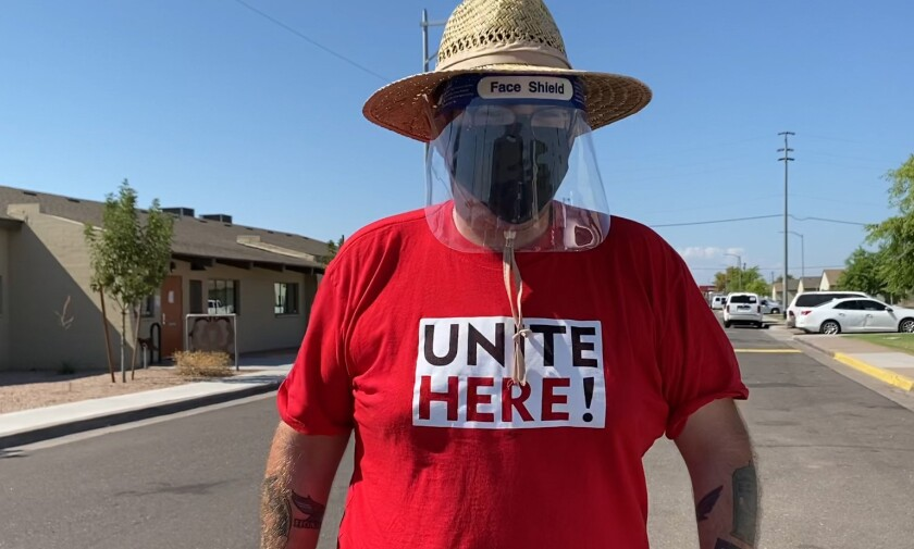"Alex Rosado of Unite Here Local 11 in Los Angeles, canvassing in Phoenix in a red ""Unite Here"" T-shirt and face shield."