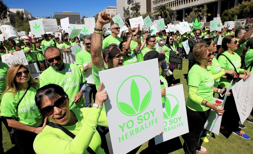 Hundreds of Herbalife distributors wearing green T-shirts gather at Grand Park in downtown Los Angeles to show their support for the beleaguered nutritional products company.