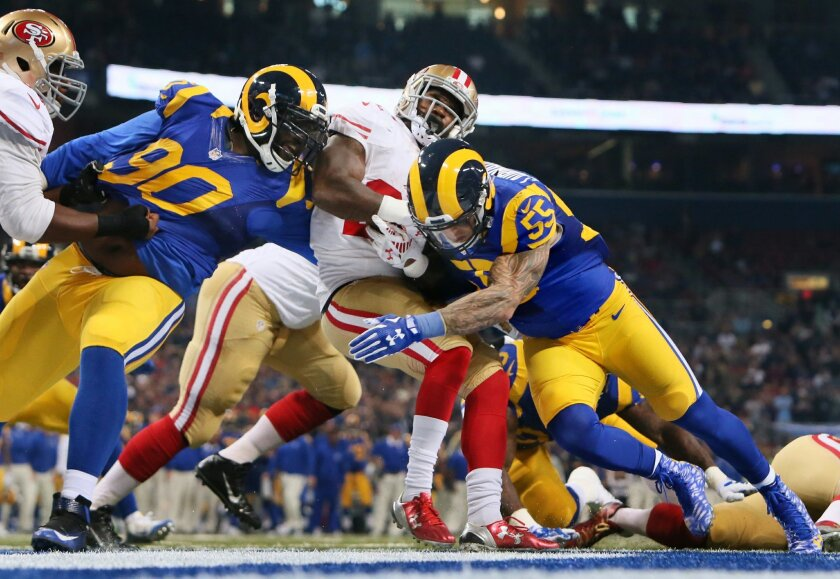 St. Louis Rams defensive tackle Michael Brockers, left, and linebacker James Laurinaitis tackle San Francisco 49ers running back Mike Davis during an NFL football game Sunday, Nov. 1, 2015, in St. Louis. (Chris Lee/St. Louis Post-Dispatch via AP)  EDWARDSVILLE INTELLIGENCER OUT; THE ALTON TELEGRAPH
