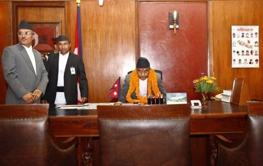 Nepal's newly-appointed Prime Minister Khilraj Regmi, center, assumes office after being sworn in in Katmandu,Nepal, Thursday, March 14, 2013.Nepal's chief judge became head of an interim government Thursday that is charged with holding elections in three months to replace the parliament whose term expired almost a year ago. (AP Photo/Niranjan Shrestha)