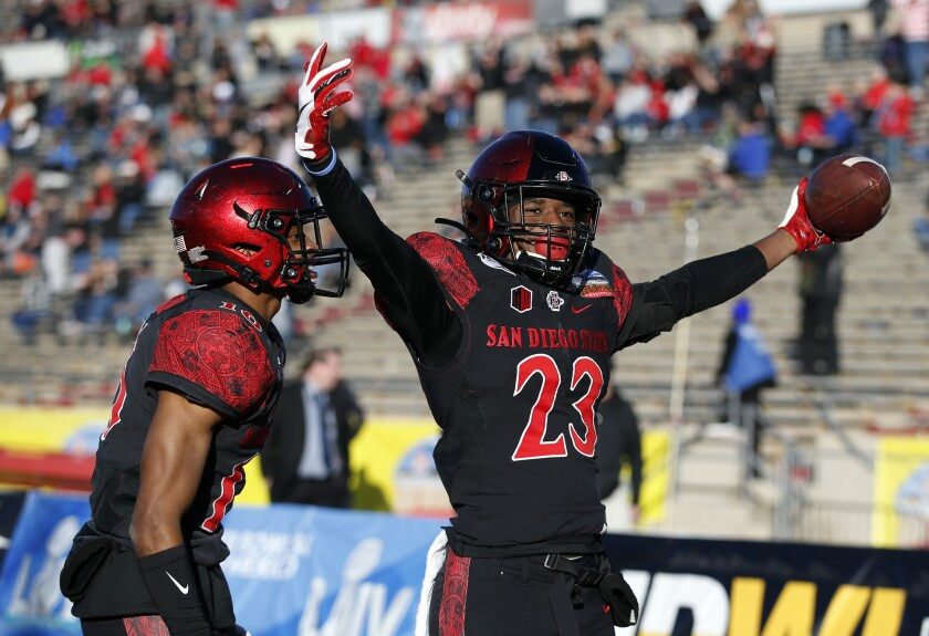 San Diego State cornerback Darren Hall (23) celebrates with teammate Luq Barcoo after scoring a touchdown on a fumble return against Central Michigan in the fourth quarter of the New Mexico Bowl.