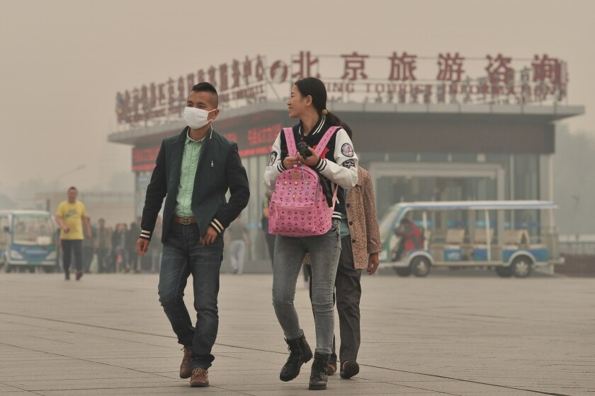 A masked man walks by the National Stadium in Beijing amid heavy smog.