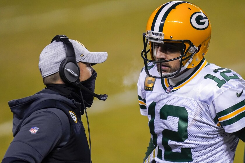FILE - In this Jan. 3, 2021, file photo, Green Bay Packers head coach Matt LaFleur, left, talks to Aaron Rodgers during the second half of an NFL football game against the Chicago Bears in Chicago. LaFleur reiterated his hope that he'd get to continue working with Rodgers this season while offering no news on the quarterback's status. (AP Photo/Charles Rex Arbogast, File)