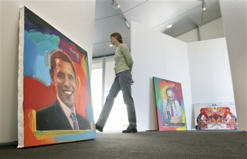Christine Mouw walks past portraits of President Barack Obama, left, Larry King, center, and other paintings as she supervises the hanging of artwork for the Peter Max exhibit at the Clinton Presidential Library in Little Rock, Ark., Thursday, Feb. 12, 2009. The pop artist's work is on three floors of the museum part of the Clinton Presidential Center for a show that begins Monday and runs through May 25. (AP Photo/Danny Johnston)