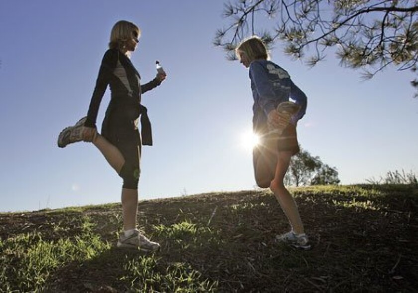 Shari Hume (left) stretched with Ashley O'Hara. Hume, who jogs every day to relieve stress, wants to run in the Boston Marathon. Hume started a foundation to provide information and raise funds for her son Parker, who has a rare childhood disease. (John Gastaldo / Union-Tribune)