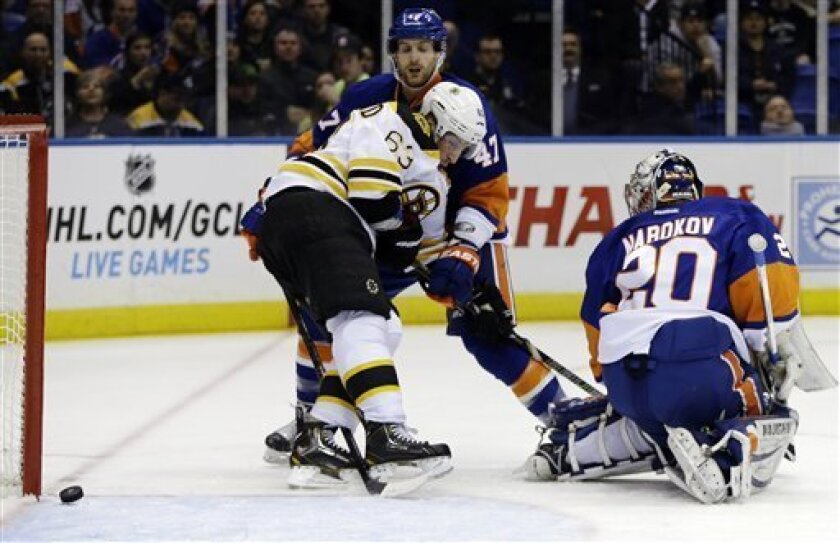 Boston Bruins left wing Brad Marchand (63) blocks New York Islanders defenseman Andrew MacDonald (47) as a goal by Bruins Adam McQuaid goes in during the first period of their NHL hockey game at Nassau Coliseum in Uniondale, N.Y., Tuesday, Feb. 26, 2013. Islanders goalie Evgeni Nabokov (20) watches