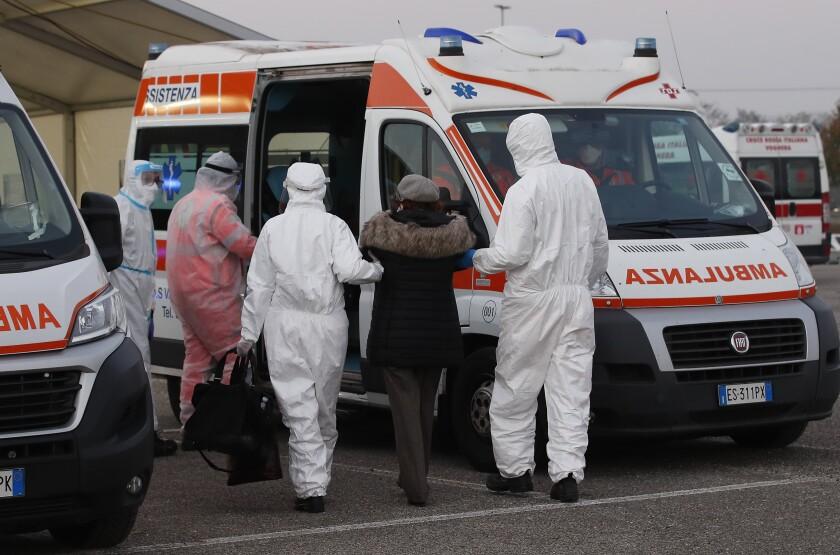Personal médico ayuda a una anciana a subir a una ambulancia
