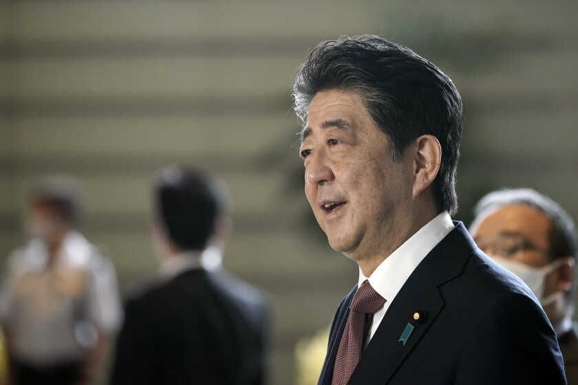 Japan's outgoing Prime Minister Shinzo Abe speaks to the media as he arrives at the prime minister's office for a cabinet meeting Wednesday, Sept. 16, 2020, in Tokyo. Abe and his Cabinet resigned, clearing the way for his successor Yoshihide Suga to take over after parliamentary confirmation later in the day. (AP Photo/Eugene Hoshiko)