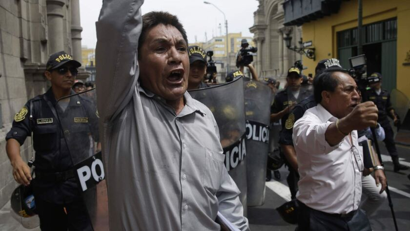 Riot police divert men shouting slogans against Peru's government outside the Government Palace in Lima on March 21, 2018.