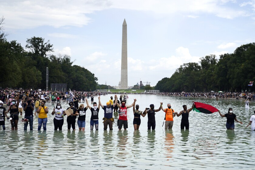 People join hands as they pose for a photo in the Reflecting Pool in the shadow of the Washington Monument.