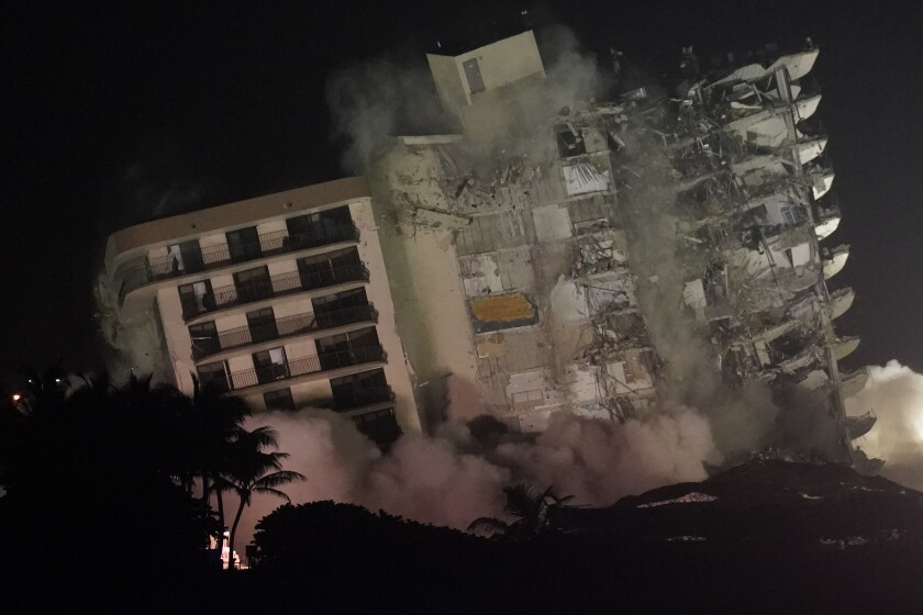 The damaged remaining structure at the Champlain Towers South condo building collapses in a controlled demolition, Sunday, July 4, 2021, in Surfside, Fla. The decision to demolish the Surfside building came after concerns mounted that the damaged structure was at risk of falling, endangering the crews below and preventing them from operating in some areas.(AP Photo/Lynne Sladky)
