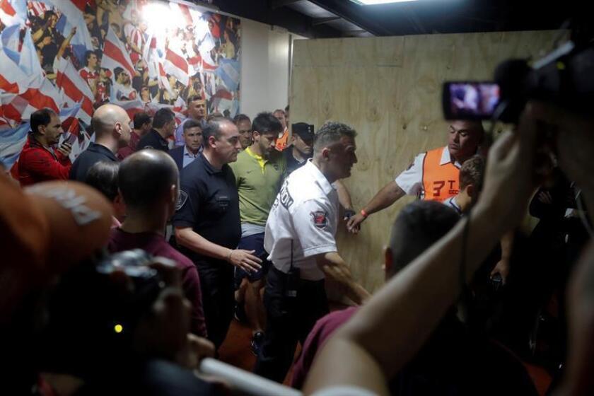 El jugador de Boca Juniors Pablo Pérez (c) sale acompañado por médicos luego que el autobús del equipo fuera atacado por aficionados de River Plate antes del partido de la final de la Copa Libertadores entre River Plate y Boca Juniors en el estadio Monumental en Buenos Aires (Argentina). EFE