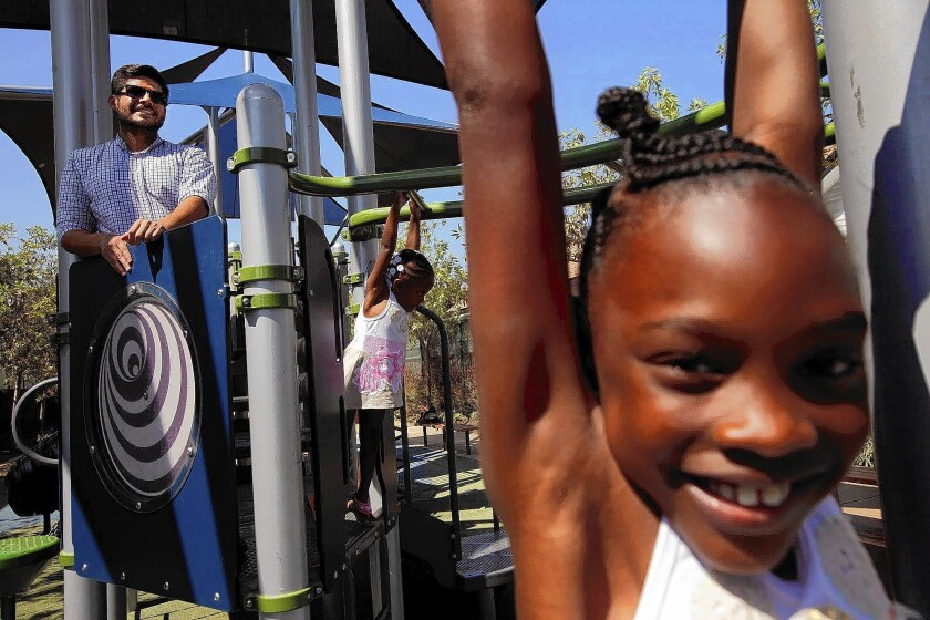"""Israel Cruz, left, of the Los Angeles Neighborhood Land Trust, watches as Kalay Swink, 2, and her sister Sanaai Flowers, 7, play in 76th Street Park. Cruz is compiling a database of small lots, alleys and other spaces that could be turned into """"parklets"""" or other green spaces."""