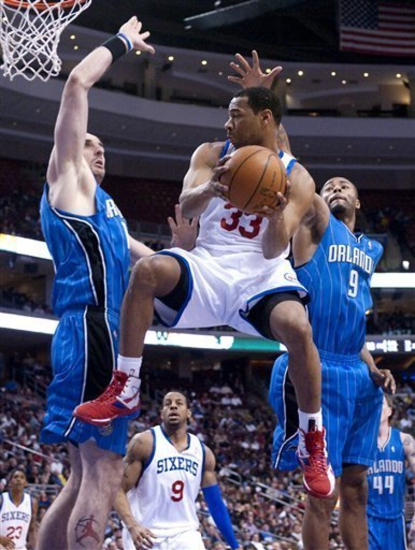 Philadelphia 76ers guard Willie Green (33) drives past Orlando Magic forward Rashard Lewis (9) and center Marcin Gortat, of Poland, in the first half of an NBA basketball game Monday, March 1, 2010, in Philadelphia. (AP Photo/Michael Perez)