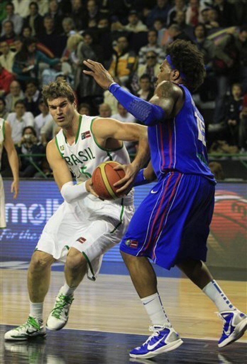 Brazil's Tiago Splitter, left, attempts to dribble past Dominican Republic's Jack Martinez during a FIBA Americas Championship semi-final basketball game in Mar del Plata, Argentina, Saturday Sept. 10, 2011. The top two finishers of the tournament get an automatic berth in the 2012 London Olympics and the next three advance to the last-chance Olympic qualifier to be held in July 2012. (AP Photo/Martin Mejia)