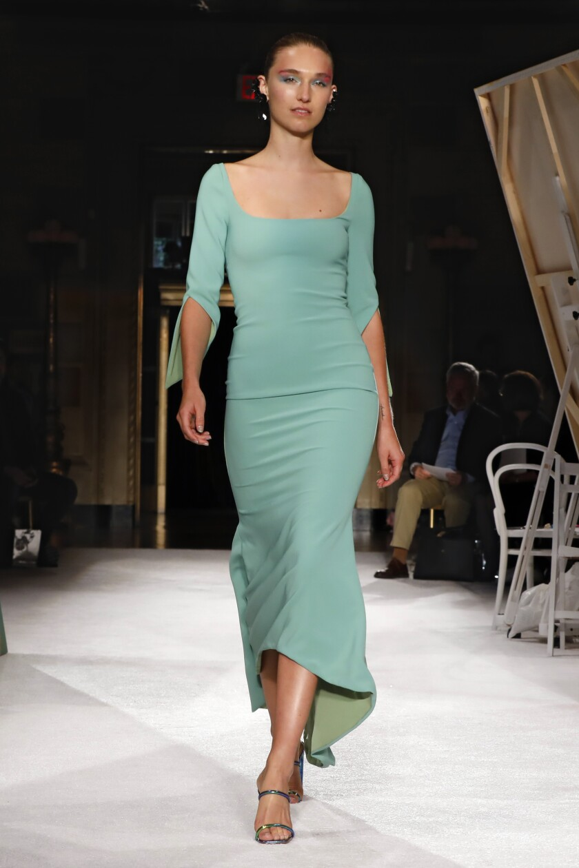A model wears a sage green dress from Christian Siriano's 2020 runway collection
