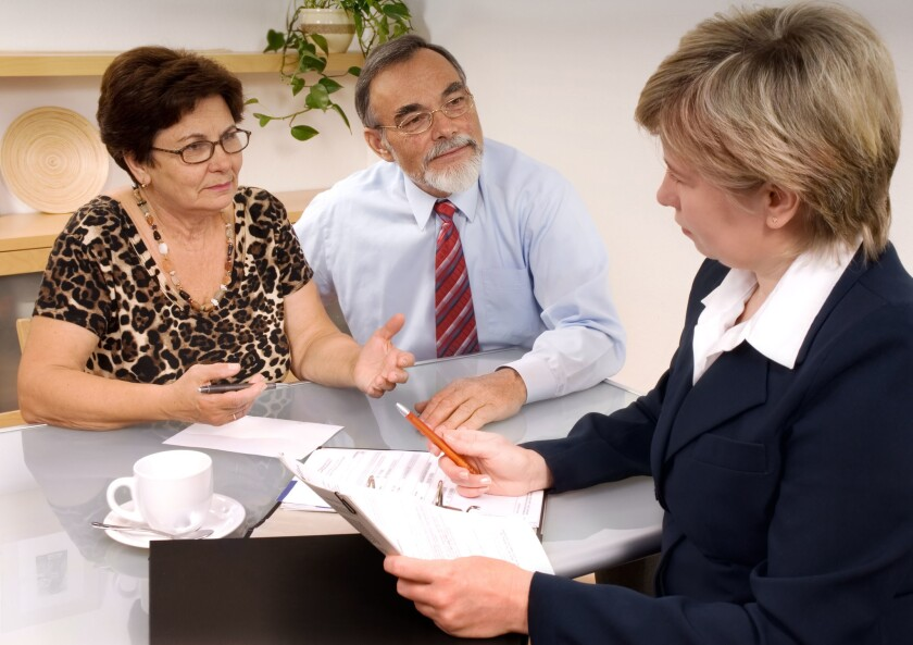 Mature couple talking to financial planner.