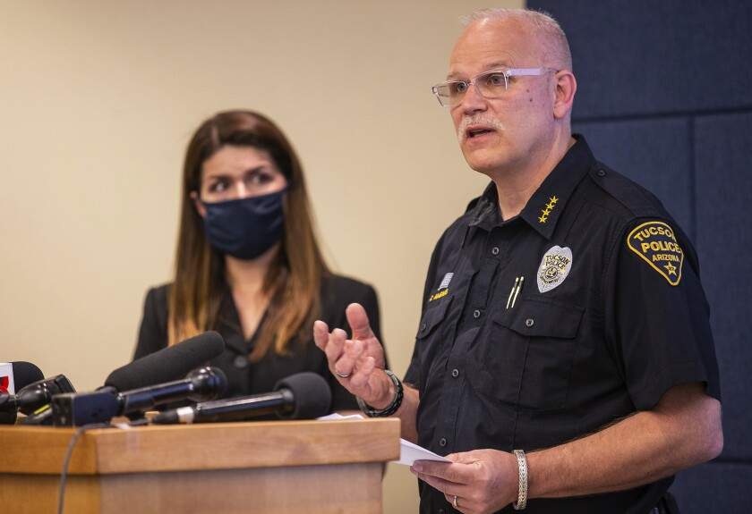 Tucson Police Chief Chris Magnus speaks as Mayor Regina Romero listens during a news conference.