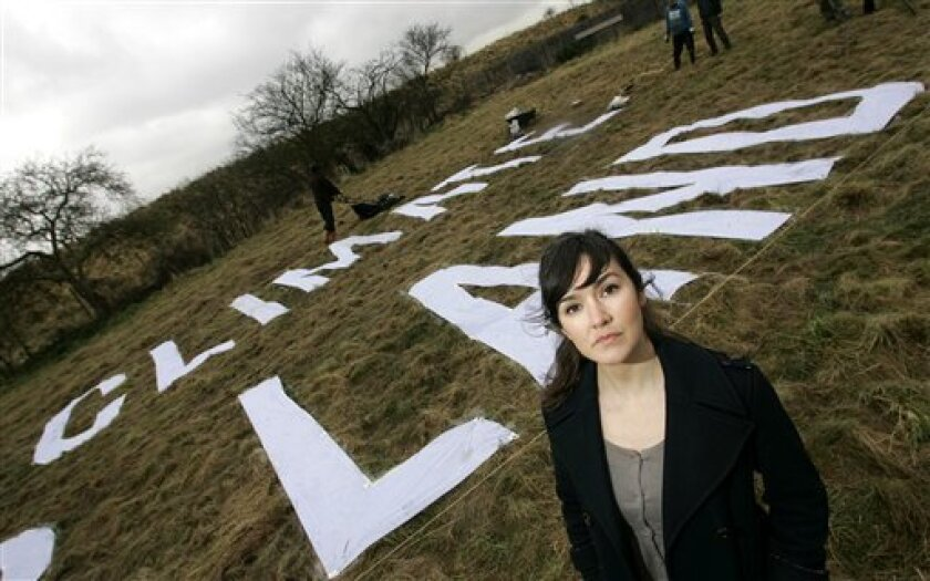 Greenpeace Climate Campaigner Anna Jones poses for photographs in front of letters of their slogan 'Our Climate Our Land', partially seen, on a plot of land in Sipson, north of Heathrow Airport, in west London,Tuesday, Jan. 13, 2009. Greenpeace revealed that it had bought a section of land on the p